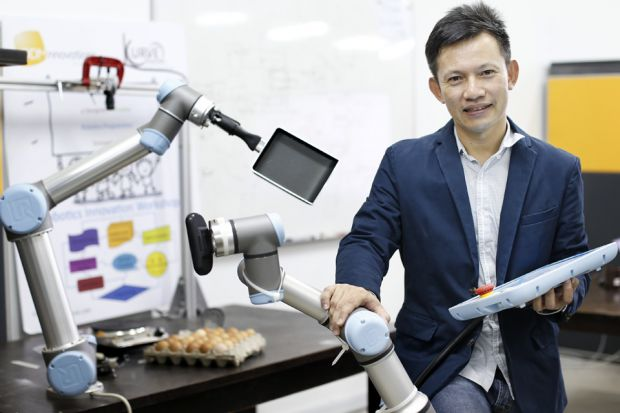 """""""Even if the initial idea sounds amazing, it is important to network and develop the idea."""" - Hui Wing Feh, director, Kurve Automation, seen here with a robot he programmed to make omelettes. (Image from Business Times)"""