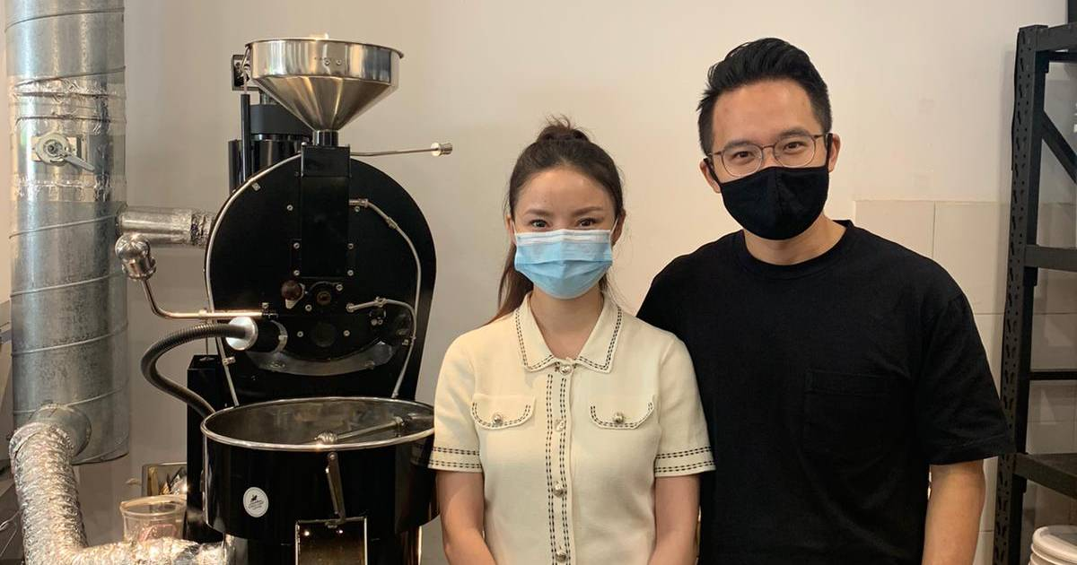 man and woman beside a coffee roaster